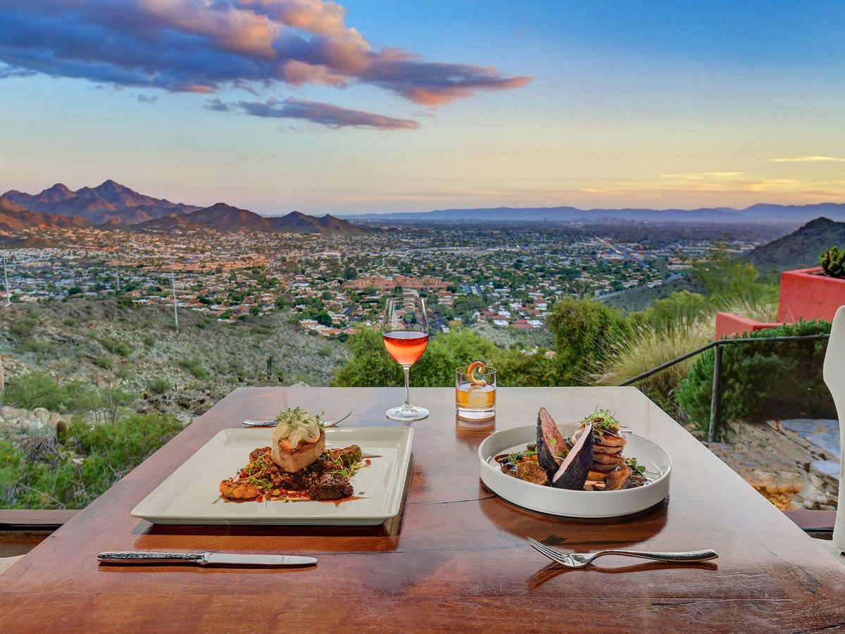 A square plate and a circular plate on a table at sunset overlooking mountains with a single stemmed wine glass filled with rosé.