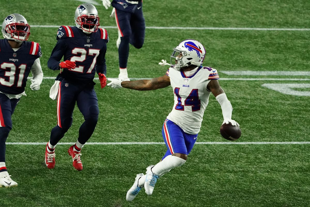 Buffalo Bills wide receiver Stefon Diggs (14) runs the ball for a touchdown against New England Patriots cornerback J.C. Jackson (27) and defensive back Jonathan Jones (31) in the half quarter at Gillette Stadium.