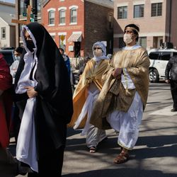 Isaac Barrera, who plays Pontius Pilate, right, joins a procession during Via Crucis in Pilsen, Friday morning, April 2, 2021. The annual Via Crucis is a Good Friday tradition that reenacts the Stations of the Cross, a Catholic devotion that recounts Jesus' passion and death.