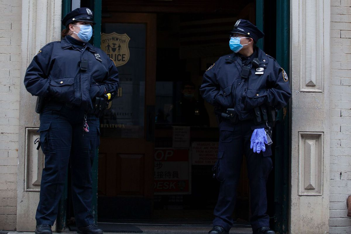 Two NYPD officers stand guard outside the fifth precinct in Chinatown.