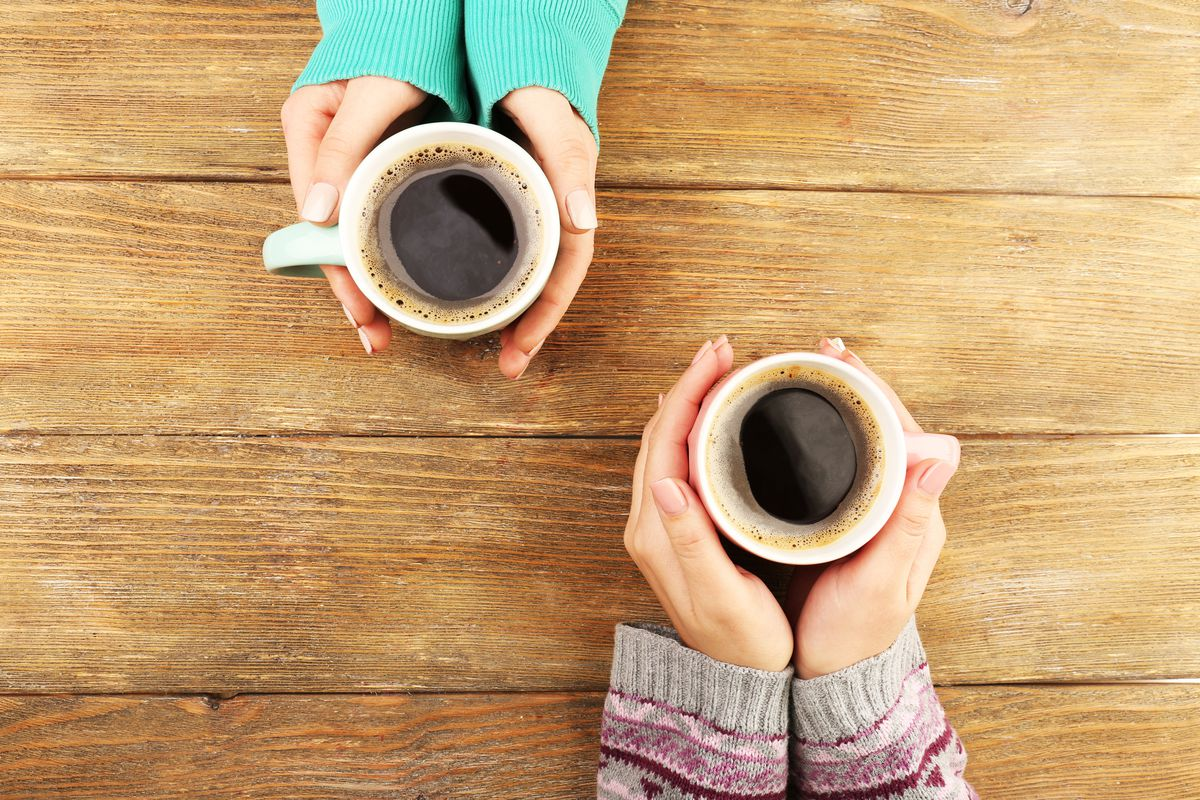 Two people hold coffee mugs over a rustic table