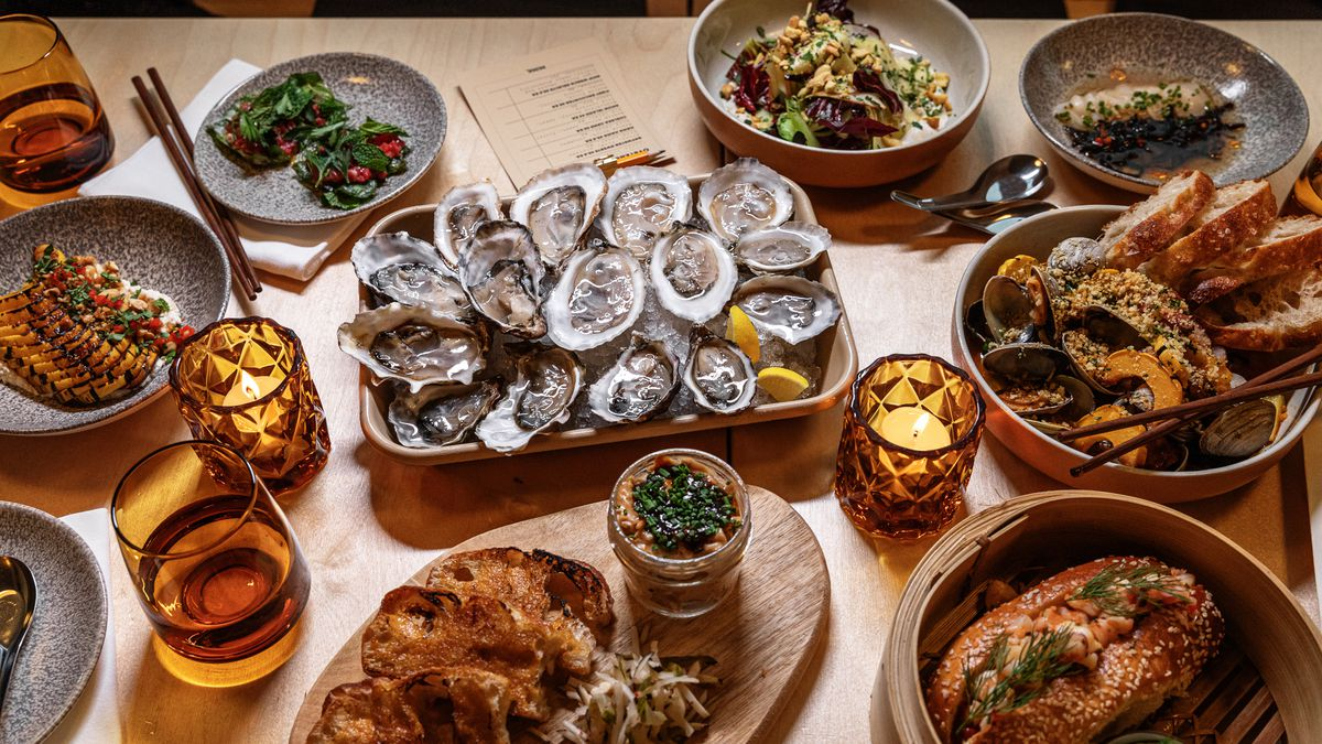 The spread of oysters and other small plates surrounded by chopsticks and amber colors glasses and candle holders at Mink.