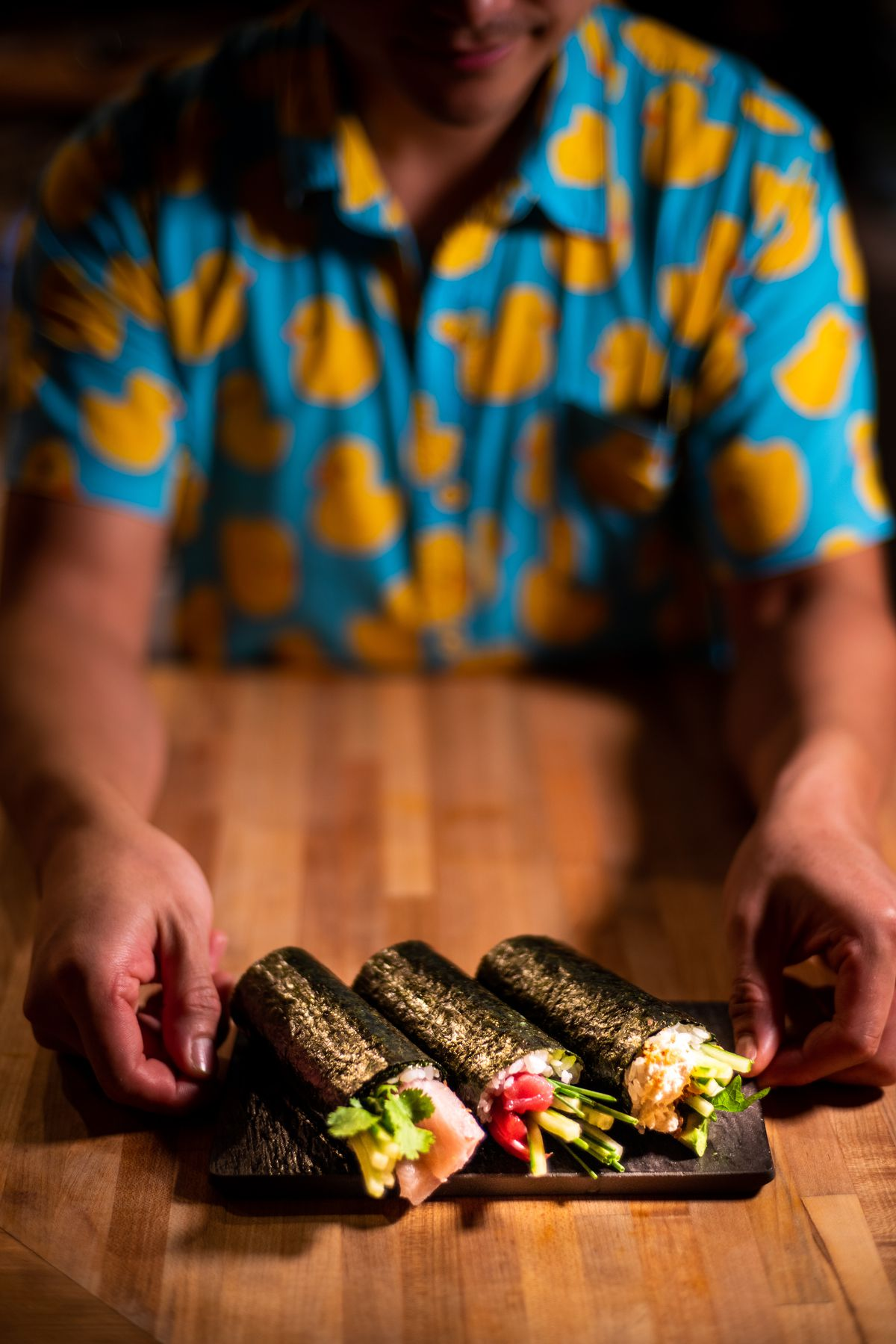 Chef presenting three hand rolls on a serving plate