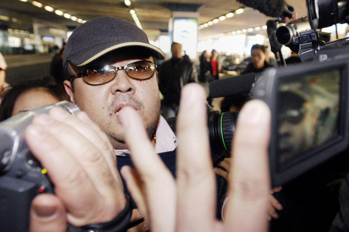 Kim Jong Nam walking among journalists at Beijing's international airport in 2007.