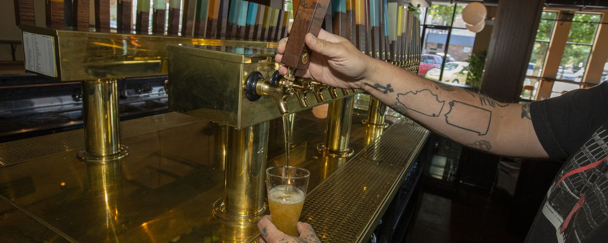 A hand pouring beer from a tap with another holding a glass collecting the nectar.