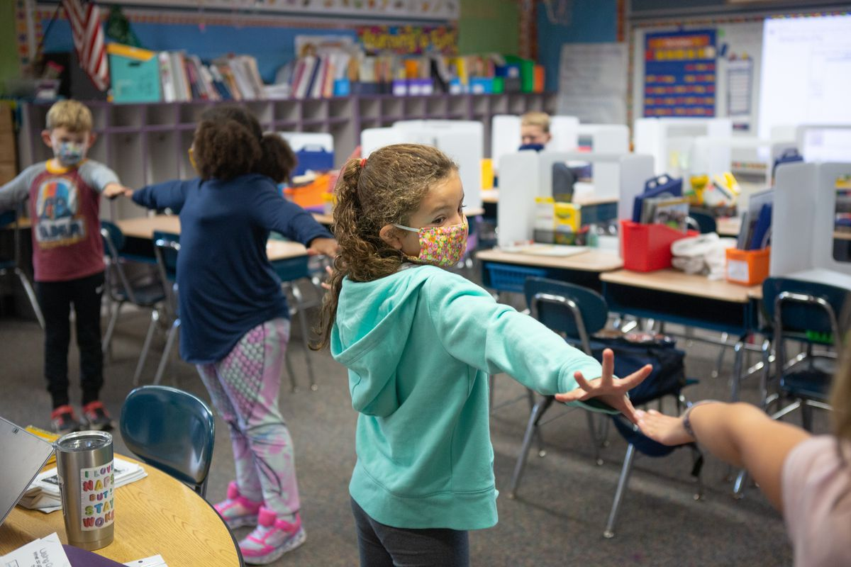 Students create distance between each other using their arms as they line up to go outside in Mrs. Cecarelliís second grade class at Wesley Elementary School in Middletown, CT, October 5, 2020.