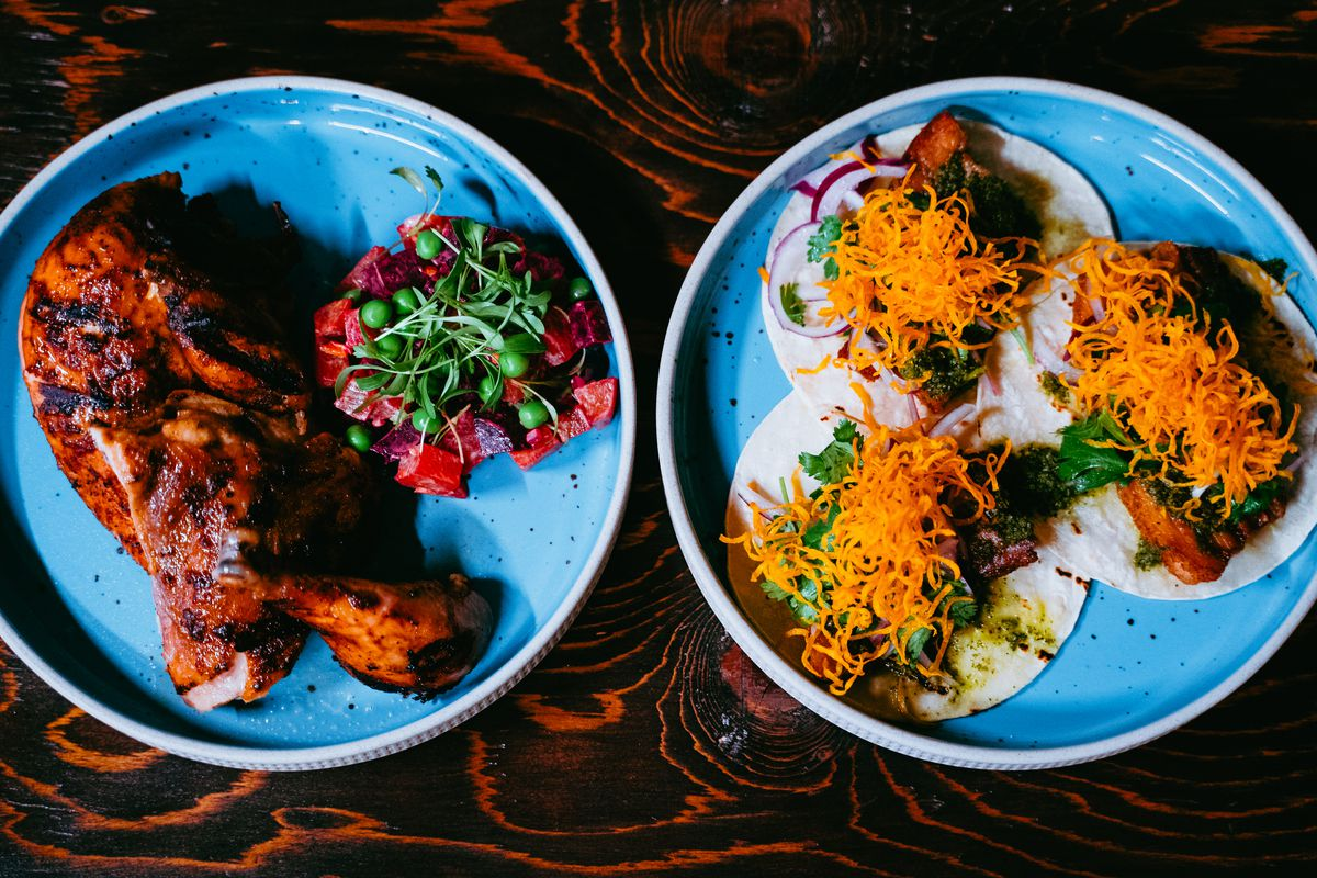 two plates, one with chicken, one with tacos