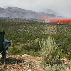 Brent Prince shoots a photo of a tanker dropping retardant on the Mill Flat fire in New Harmony on Sunday. Eleven structures burned over the weekend, but no injuries have been reported.