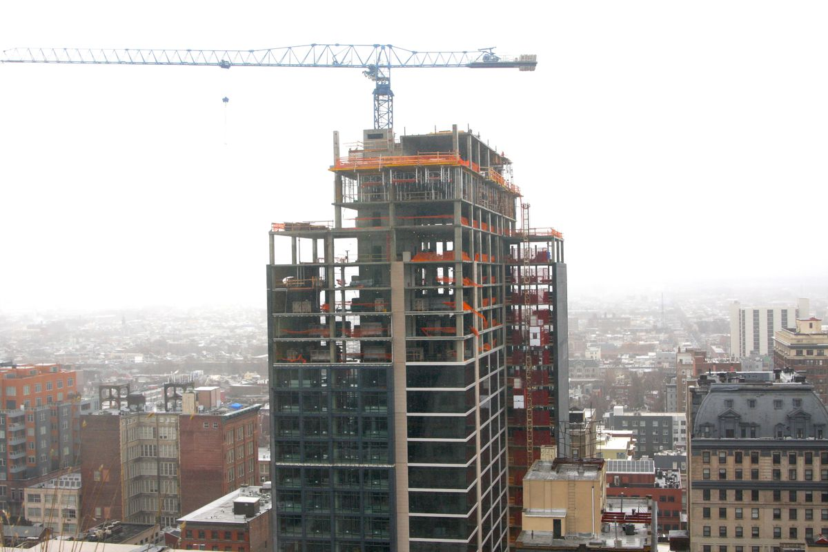 A view of 1213 Walnut tower under construction with a crane on top.