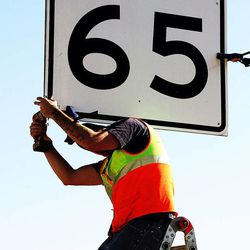 Stephan Foster of UDOT removes a 65 mph sign to change it to 70 mph on I-80 west of Salt Lake City, Monday, Dec. 8, 2014.