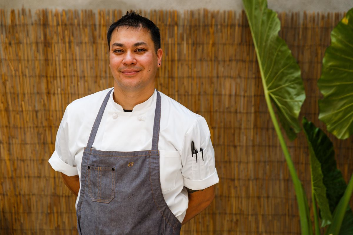 Chef Eric Tran stands for a portrait in his chef's whites and an apron near a large green plant