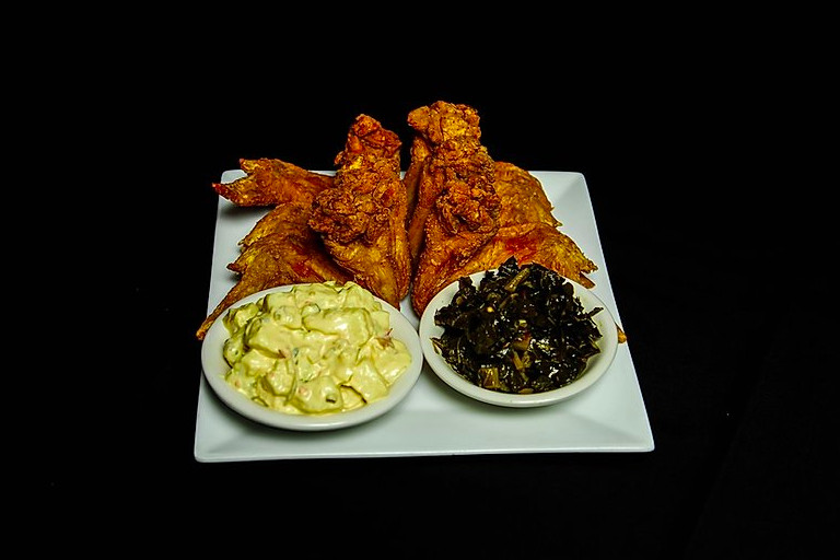 Fried chicken sits on a white plate on a black background, accompanied by small white bowls of potato salad and collard greens