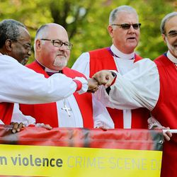 Presiding Bishop-elect Michael Curry, of North Carolina, and the Rt. Rev. Mark M. Beckwith, bishop of Newark, share a moment of fun during a rally against gun violence Sunday, June 28, 2015, from the Salt Palace Convention Center to Pioneer Park and back in Salt Lake City.