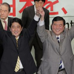 Former Japanese Prime Minister Shinzo Abe, left, joins hands with a contender Shigeru Ishiba after winning the party leadership election of Japan's Liberal Democratic Party in Tokyo Wednesday, Sept. 26, 2012. Abe, known as a hawk and nationalist, defeated ex-defense chief Ishiba in a run-off election Wednesday by a vote of 108-89 to become president of the main opposition Liberal Democratic Party.