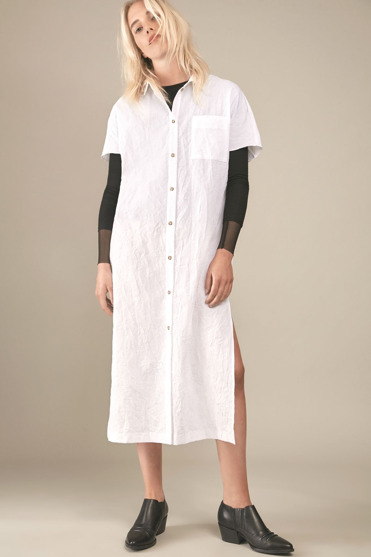 White blonde model wearing oversized white shirt dress with black ankle boots