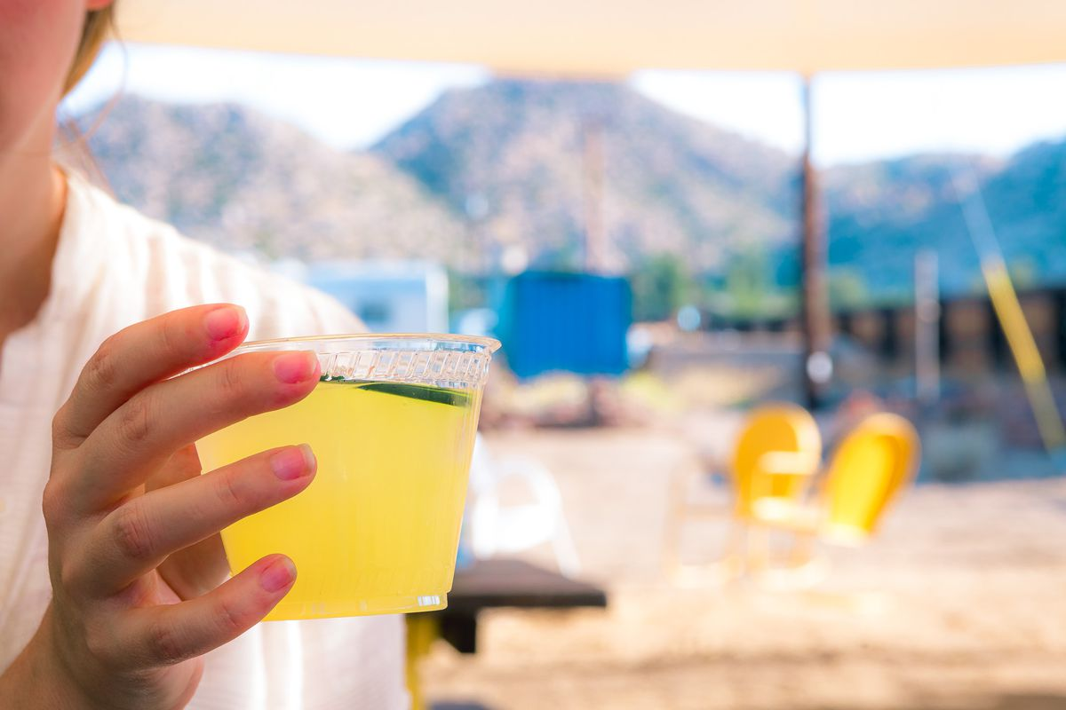 A woman holds a margarita in her hand during daylight in a desert town.