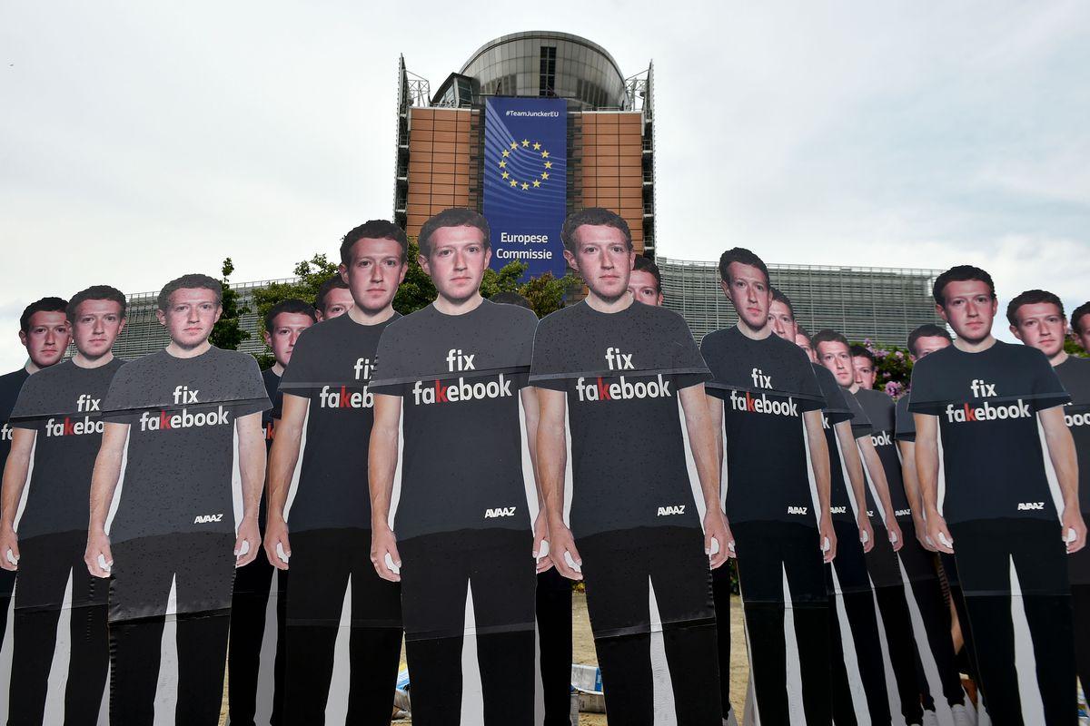 Cutouts of Facebook CEO Mark Zuckerberg at a protest.