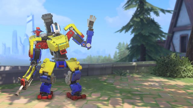 A brightly colored, Lego-style Bastion waves on the map Eichenwald in a screenshot from Overwatch.