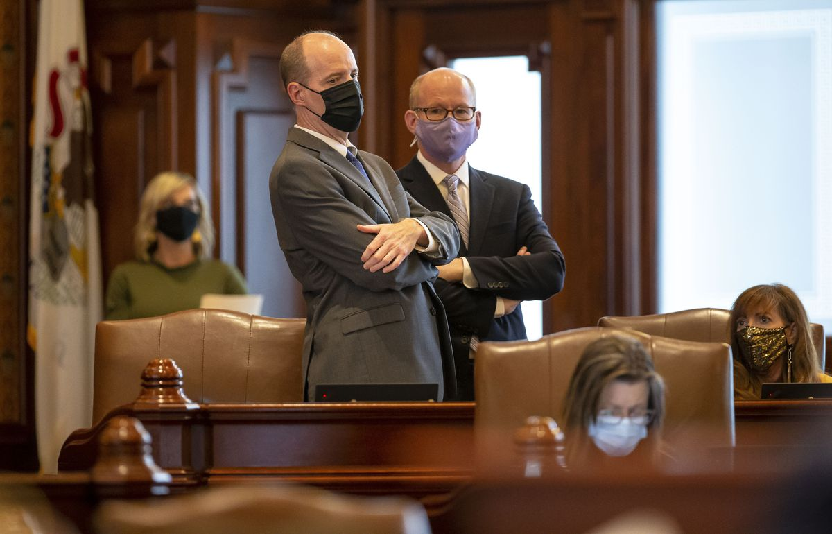 State Senate President Don Harmon, D-Oak Park, right, talks with state Sen. Bill Cunningham, D-Chicago, left, during debate on the energy proposal in the Senate on Monday.