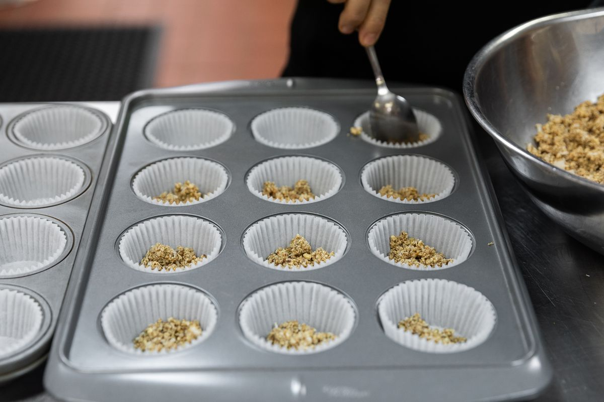 The cupcake tray has paper cupcake holders in each slot and they're half-filled with loose granola.