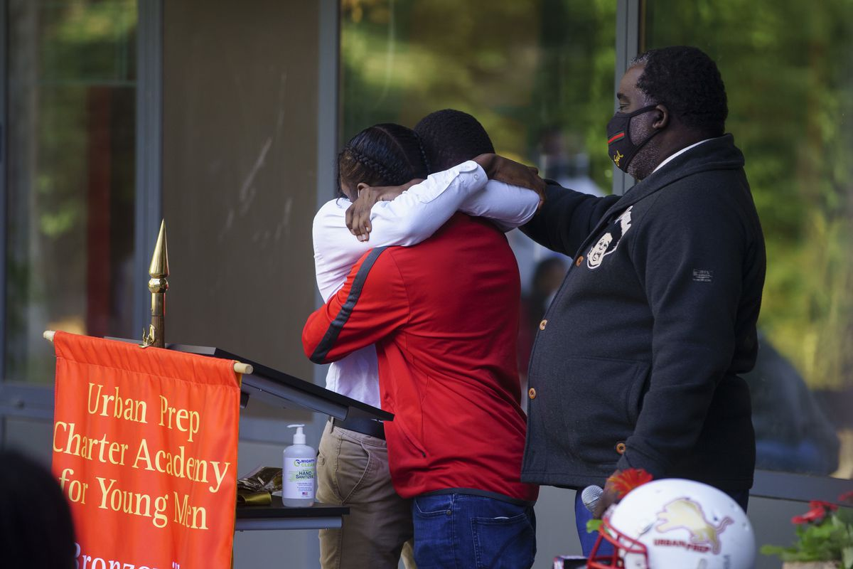 Two classmates hug one another after giving remarks during a memorial for Rashad Verner at Urban Prep Academy High School Bronzeville Campus.
