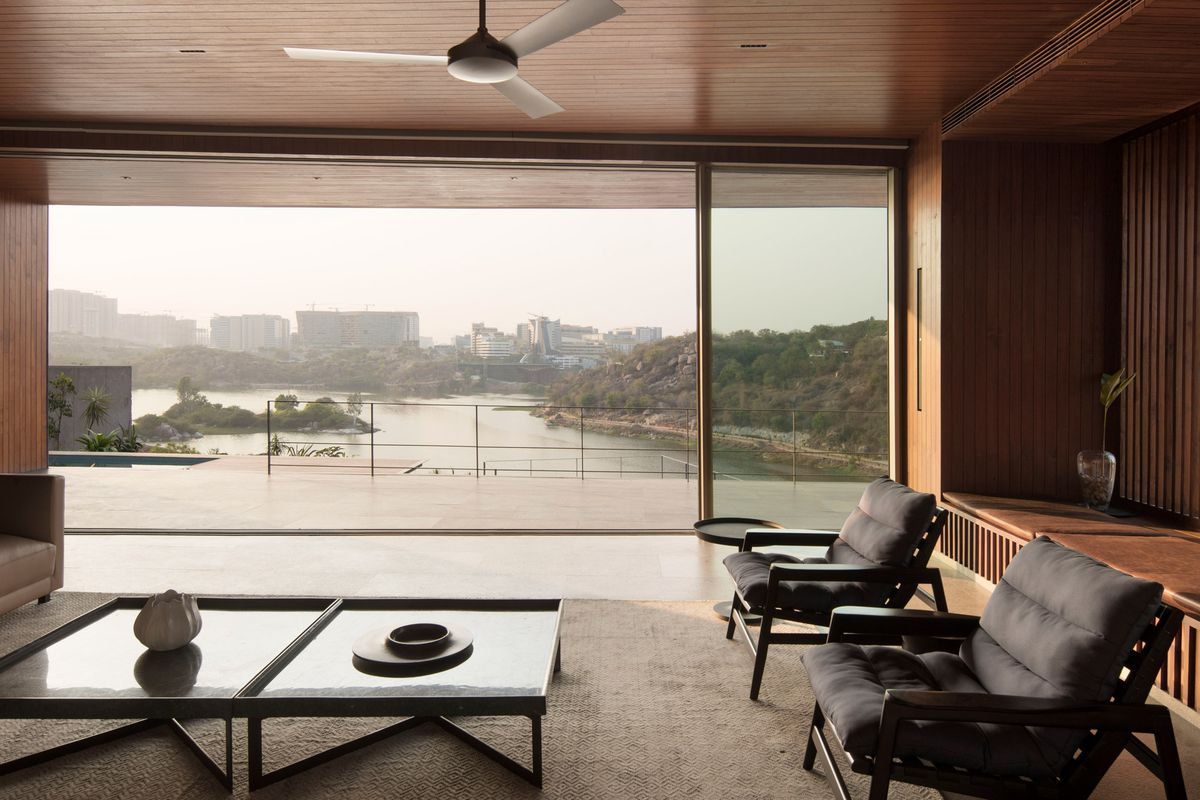 An open living room features two armchairs, an expansive coffee table, and glass walls opening onto a terrace with lake views.