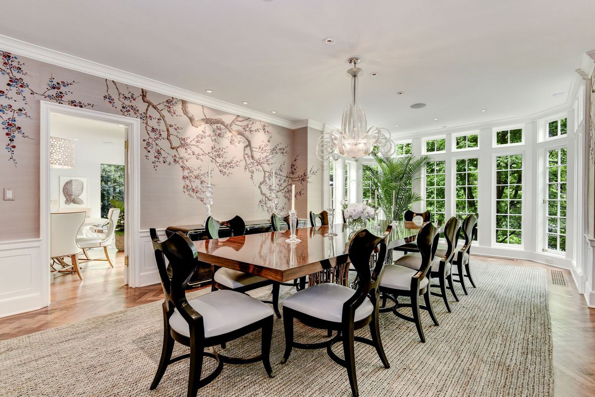 A large dining room table seats 10 in a room with windows, a chandelier, and cherry blossom wallpaper.