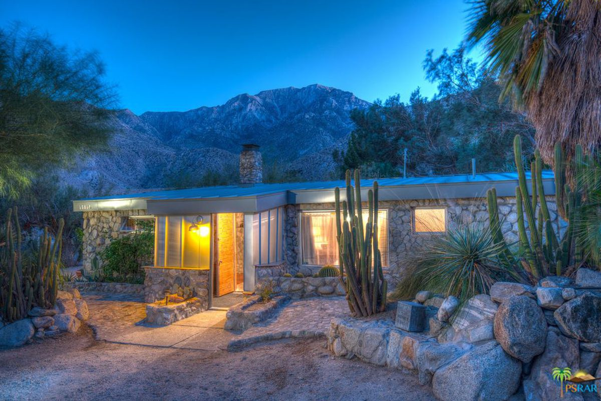 Exterior night shot of a low-profile stone cabin with cacti landscaping and mountains as a majestic backdrop.
