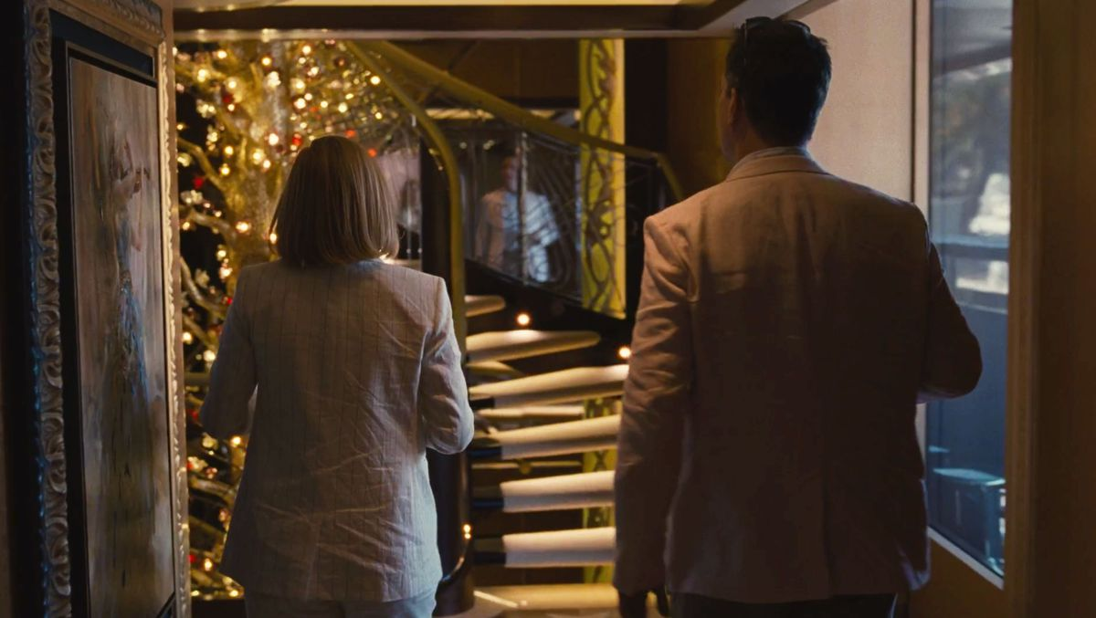 A scene from the Succession Season two finale. Shiv Roy and her husband Tom walk towards a staircase on a yacht that is decorated with an illuminated tree.