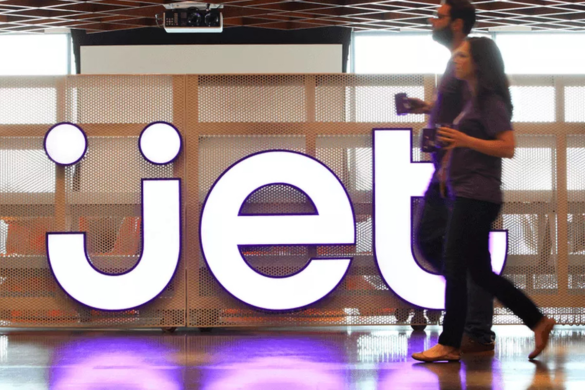 People walk past a company logo inside Jet.com's Hoboken, N.J. headquarters.