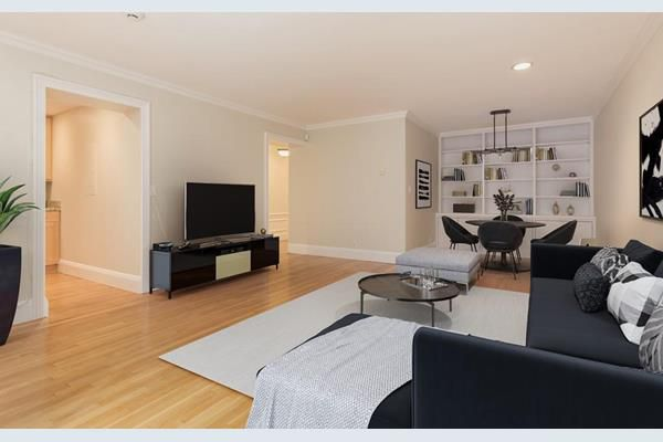 A living room-dining room area with furniture facing a TV, and there's a table and chairs off to the side.