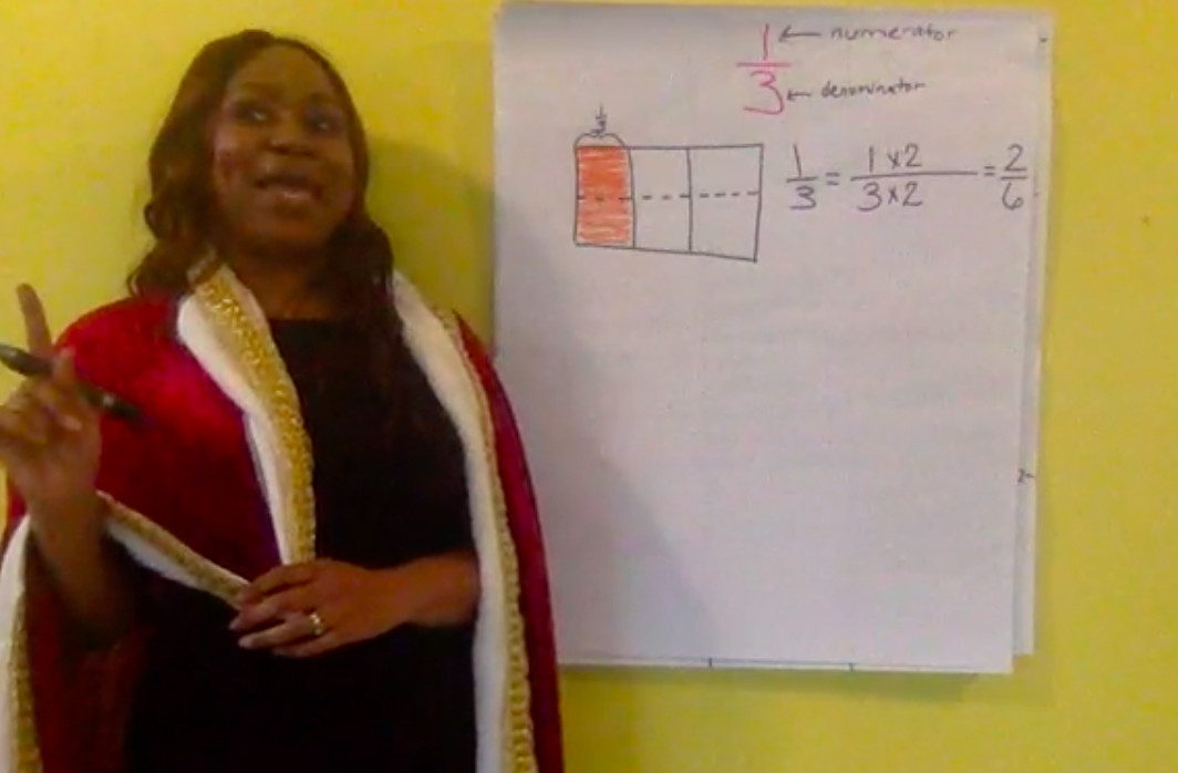 """Keiya Graves-Garrett, a math teacher advisor for Shelby County Schools, solves an equivalent fraction problem wearing her """"thinking cape"""" during her TV lesson geared to fourth-grade students."""