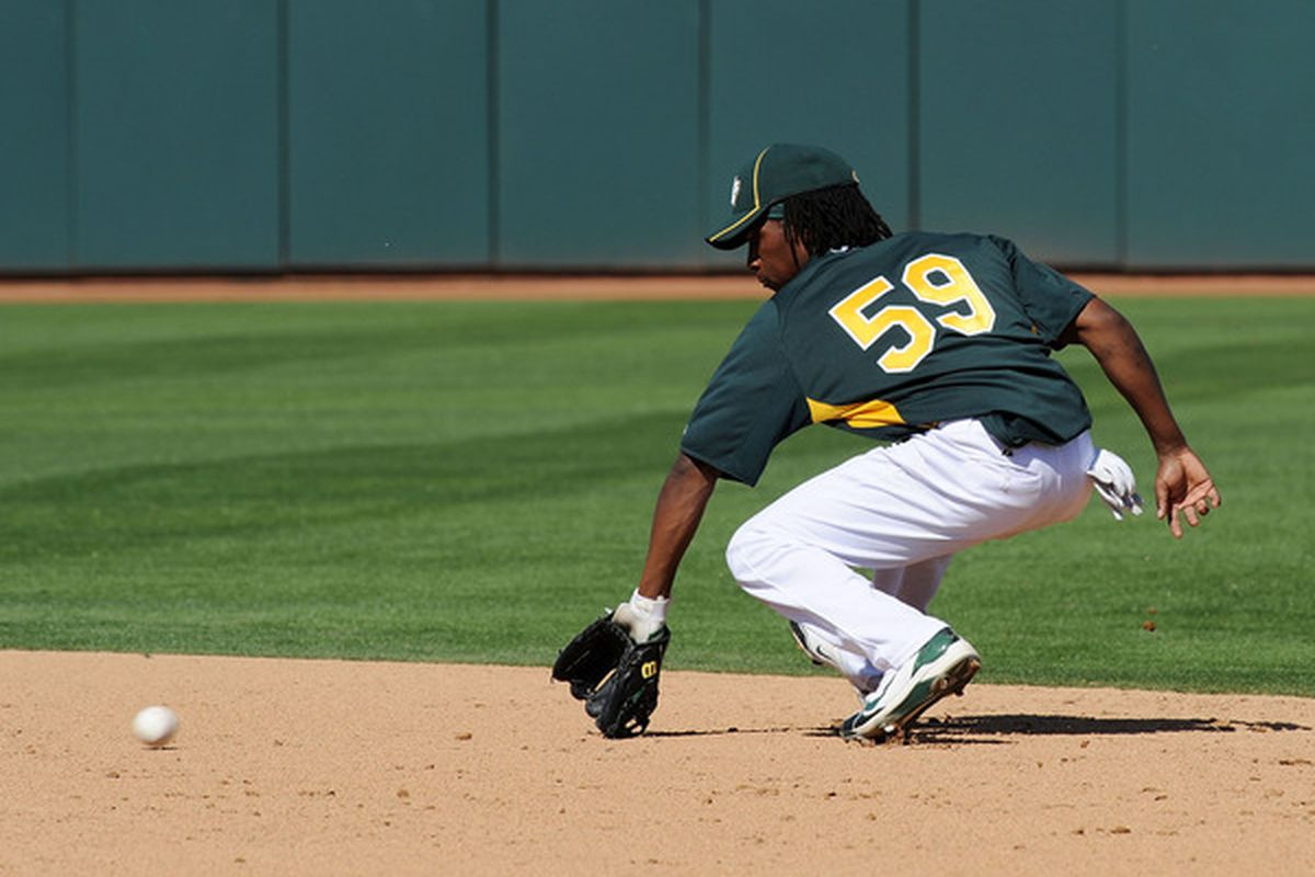 Jemile Weeks of the Oakland Athletics makes a back hand stop on a ground ball against the Texas Rangers at Phoenix Municipal Stadium on March 4, 2011 in Phoenix, Arizona.  (Photo by Norm Hall/Getty Images)