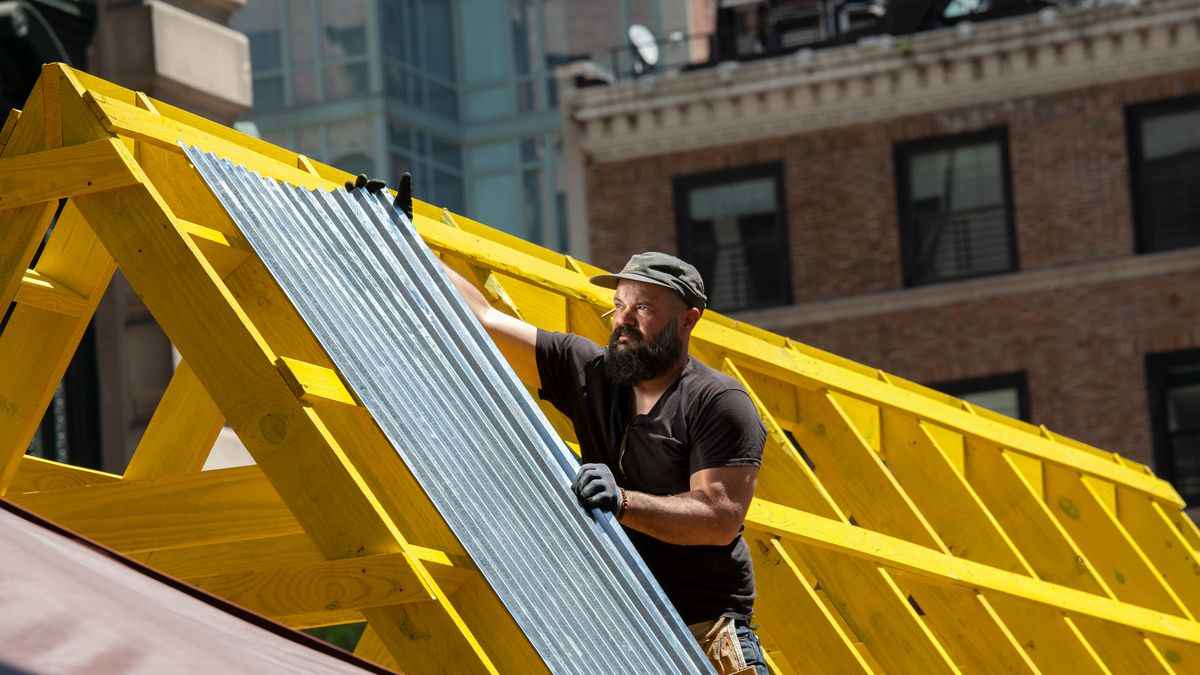 A worker helps build an outdoor eating area along 32nd Street in Korea Town, May 18, 2021.