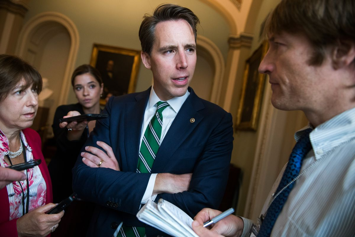 Senator Josh Hawley, standing with his arms crossed, speaks with reporters.