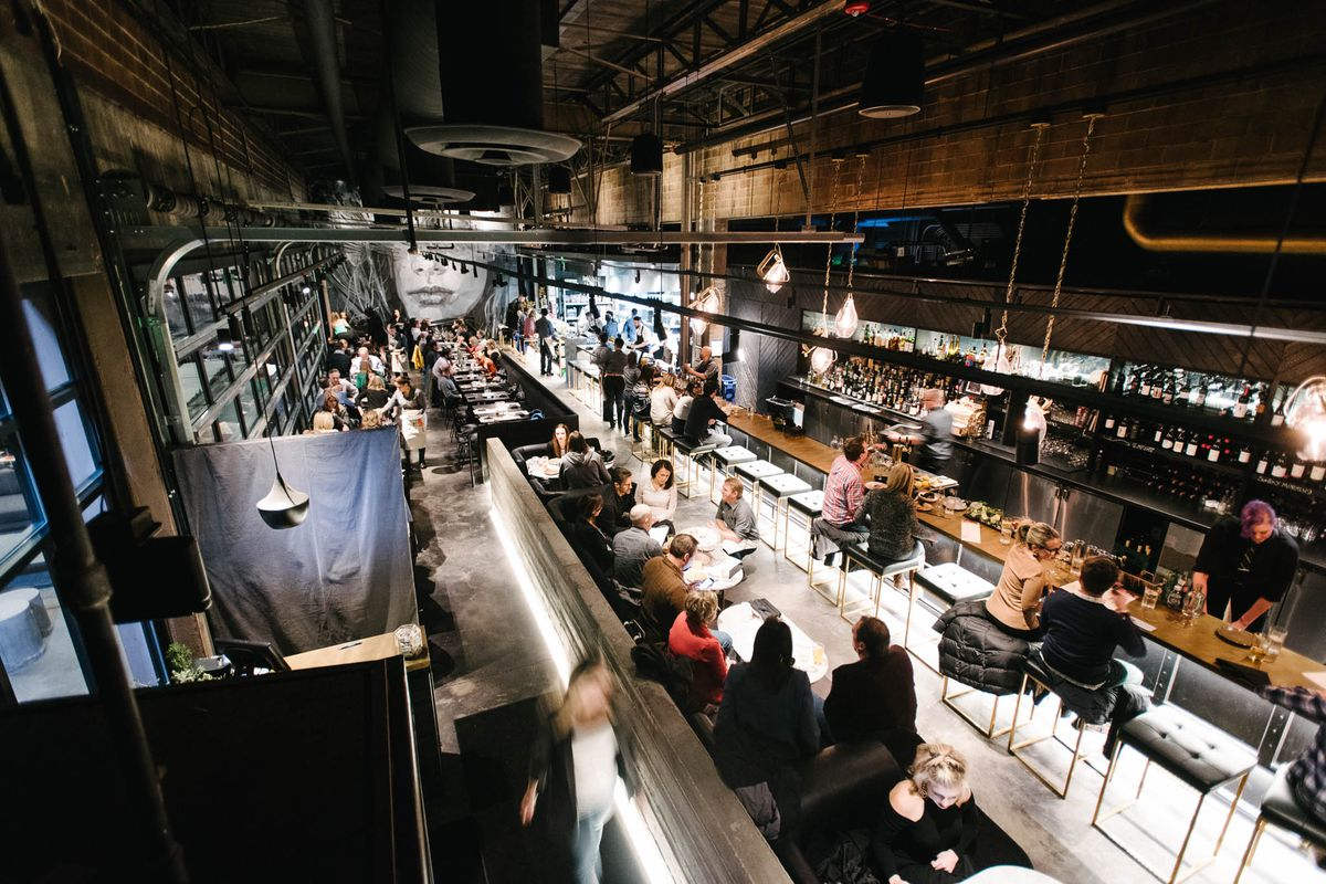A photo of Mister Tuna showing the restaurant's long bar, closed garage doors and diners at tables in the center of the space