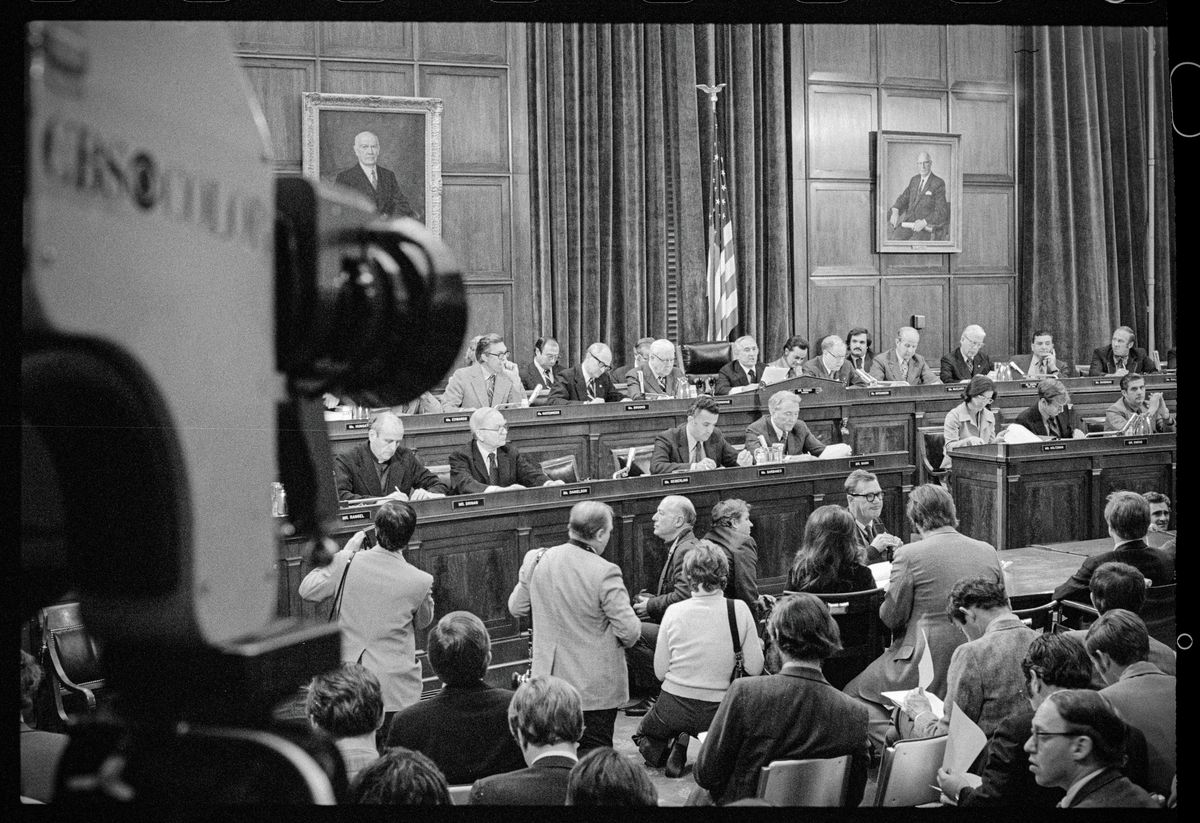 An archival photograph of the first impeachment hearing against President Nixon in 1974 shows a CBS camera in the foreground and the empaneled members of Congress plus audience members in the congressional chamber.