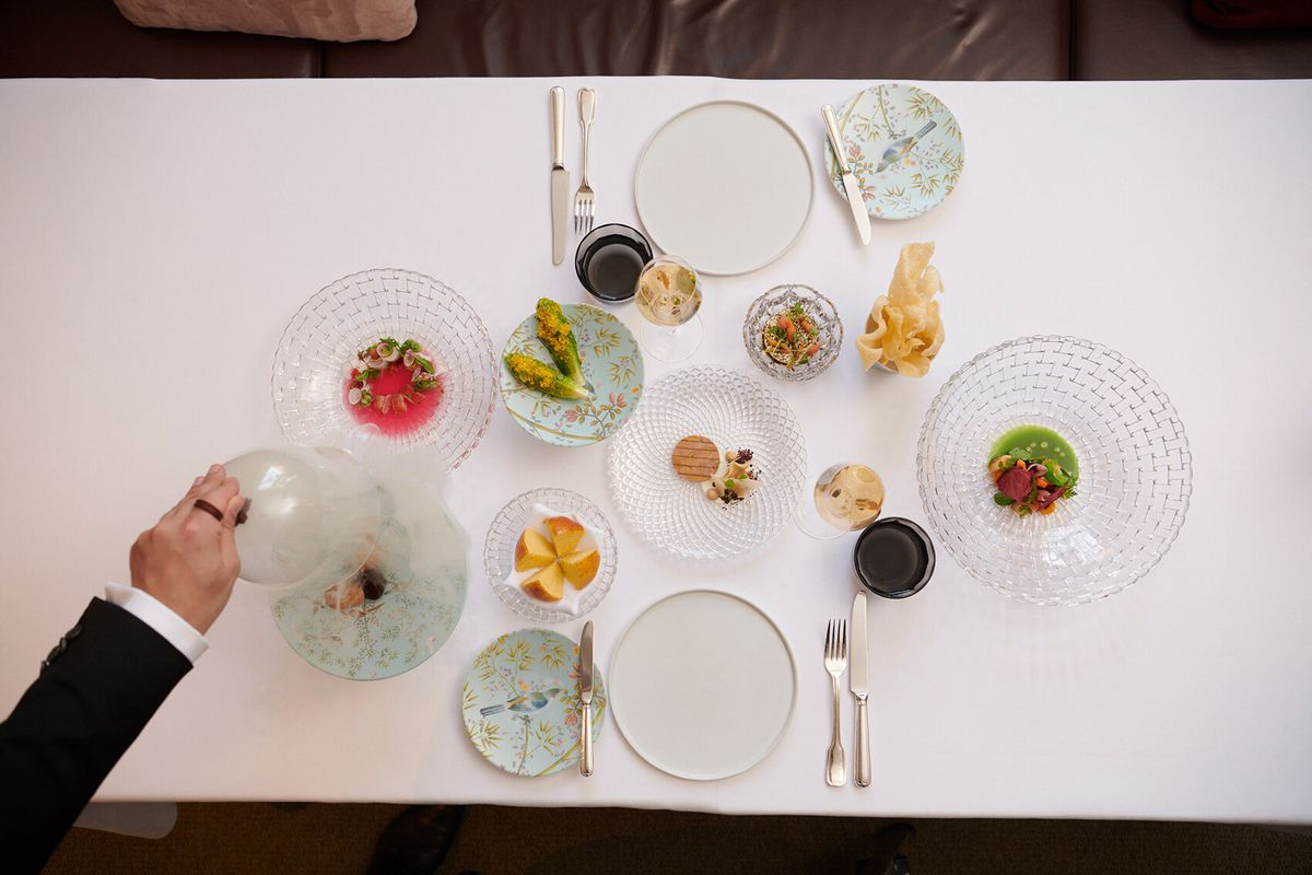 Delicate dishes of elegant food arranged on a table; the outstretched arm of a person wearing a suit lifts a cloche