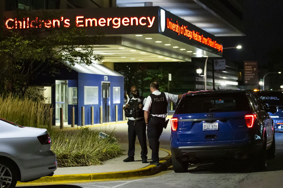 Chicago police personnel chat outside Comer Children's Hospital on the South Side after a 4-year-old boy was shot in the head Friday night in the 6500 block of South Ellis Avenue in Woodlawn.