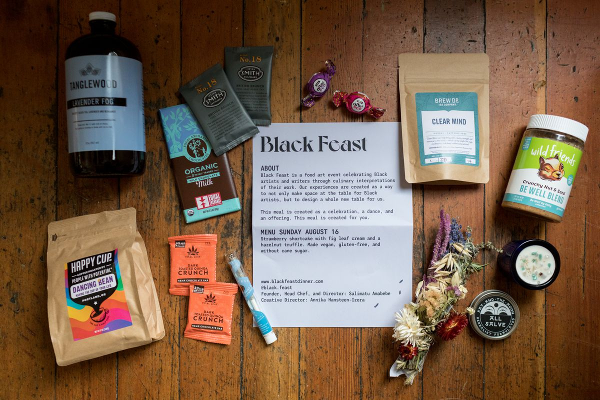 Chocolate bars, coffee, tea, chai concentrate, flowers, a jar of nut butter, and a container of salve atop a wooden tabletop.