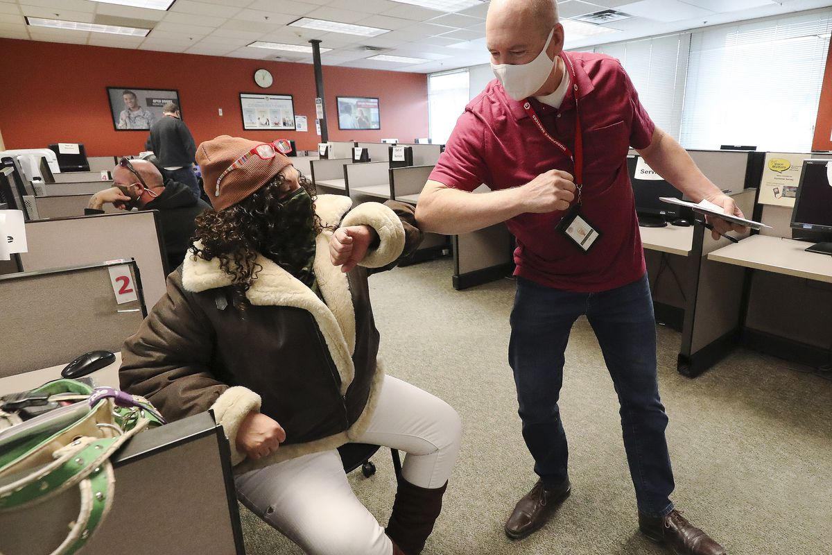 Jessica Barona, left, bumps elbows with B. BK Keown, Department of Workforce Services employment counselor, at the department's office in Salt Lake City on Friday, Dec. 18, 2020. Barona was able to get a job this morning with the help of Keown.