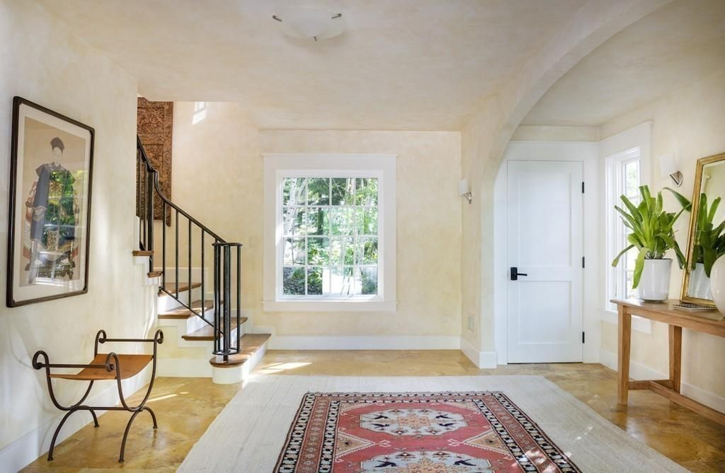 A spacious entry foyer with a staircase off it and a large rug on its floor.