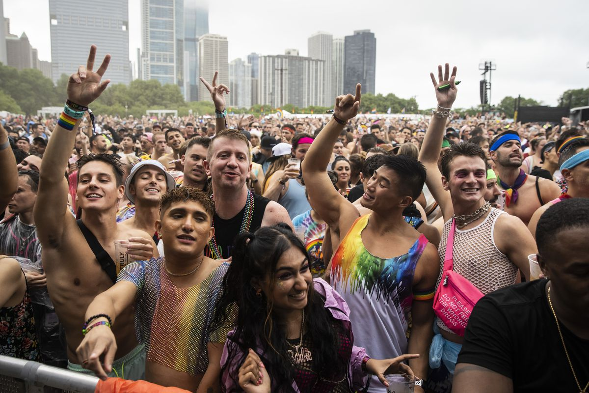 Festival-goers dance in the rain Saturday afternoon during Pride in the Park in Grant Park.