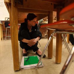 Daryllin Zitting, a Taylorsville High School student in Steve Woolley's physics class, sits under her desk during an earthquake drill as part of The Great Utah ShakeOut, Tuesday, April 17, 2012.