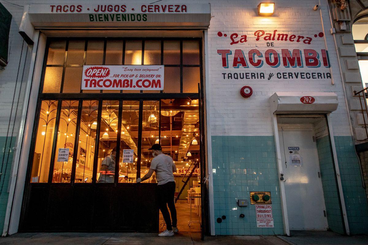 Two men shut the gate at Tacombi