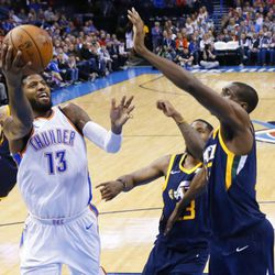 Oklahoma City Thunder forward Paul George (13) shoots in front of Utah Jazz forward Royce O'Neale, center, and center Ekpe Udoh, right, during the fourth quarter of an NBA basketball game in Oklahoma City, Wednesday, Dec. 20, 2017. Oklahoma City won 107-79.