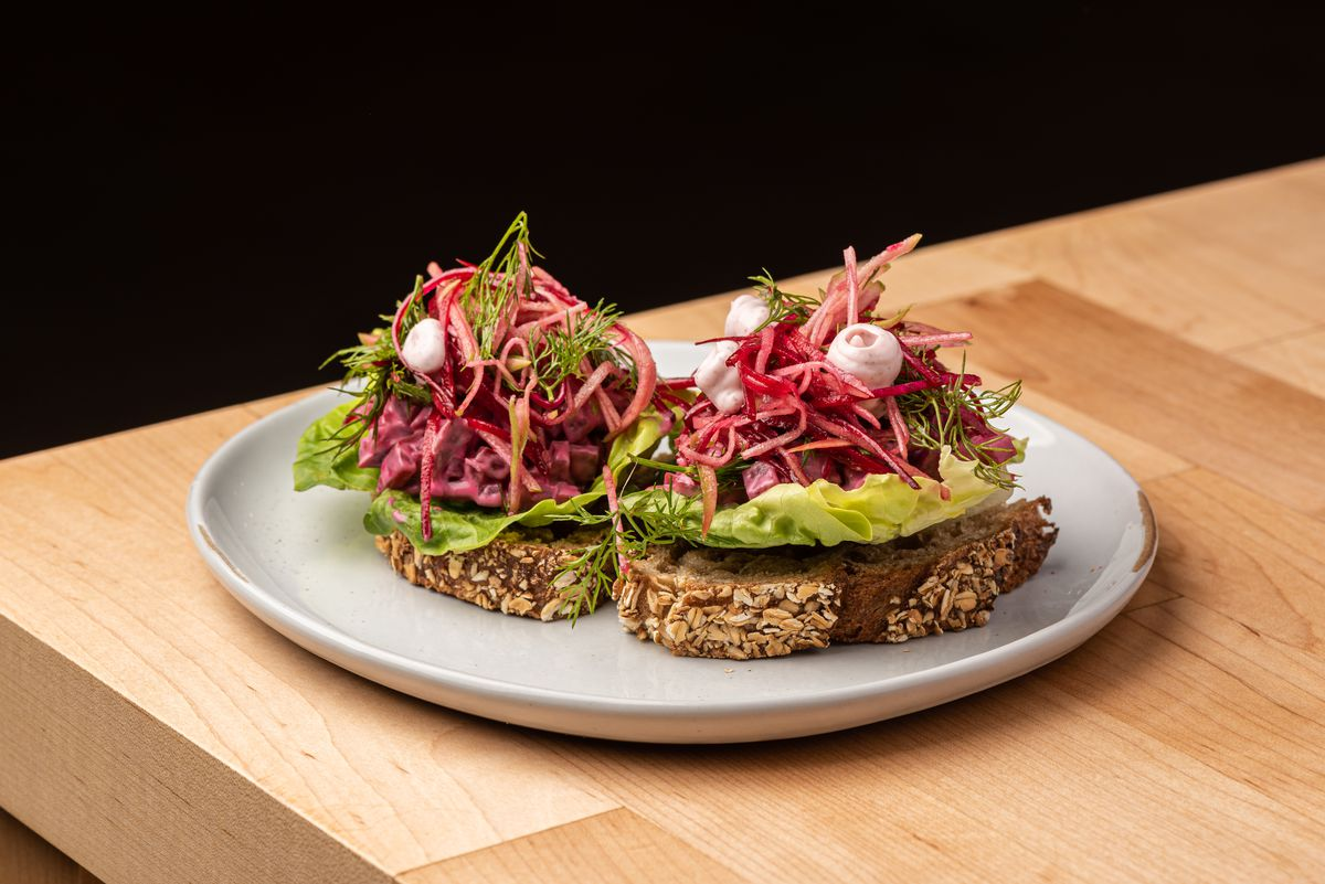 Dried beet roots on brown seeded bread atop a wooden table.