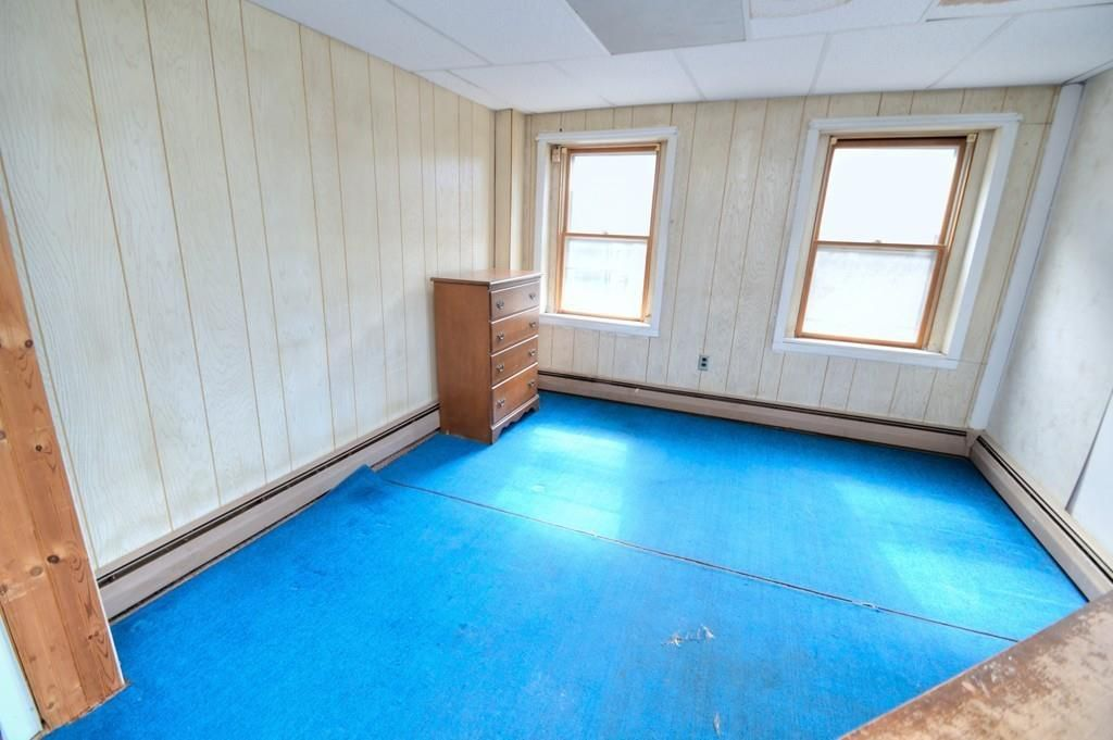 Another similarly sized—and similarly empty—bedroom with two windows.