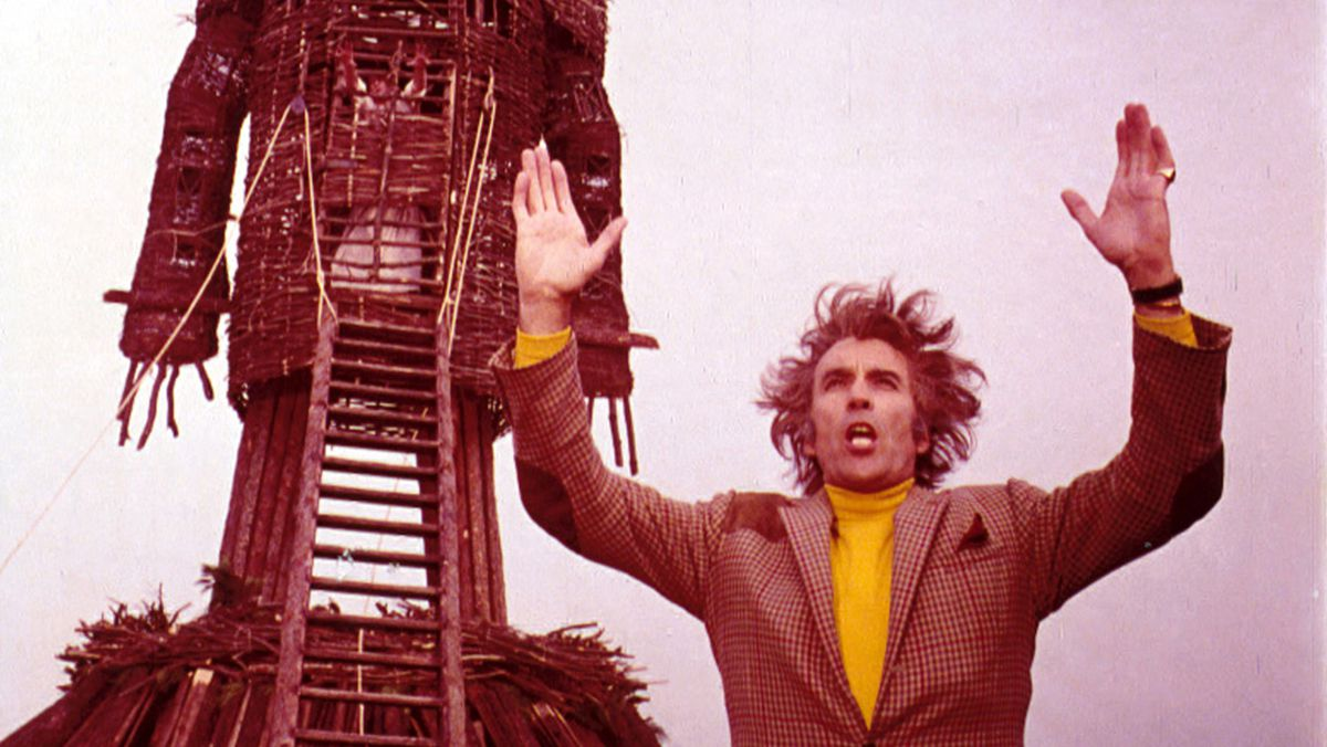 Lord Summerisle (Christopher Lee) raised his arms in front of the wicker man.