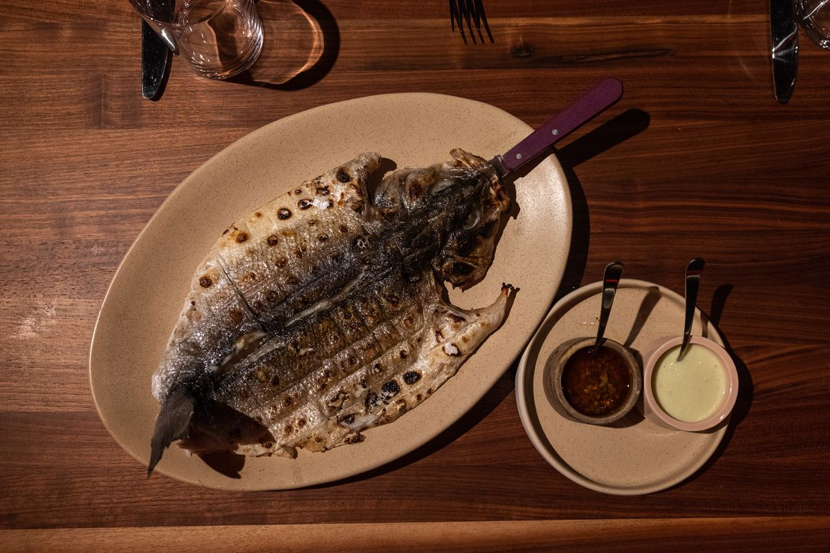 A fire-roasted fish on a plate next to two dishes of sauce at Magnet.
